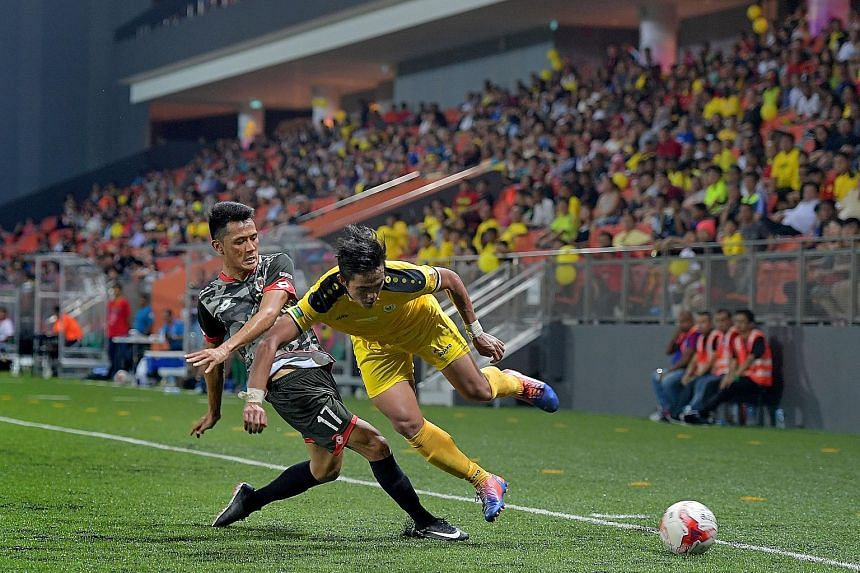Hazwan Hamzah of DPMM (left) sends Tampines' Hafiz Sujad tumbling. The Stags won 2-0 in their first game back at their old home ground since 2011.