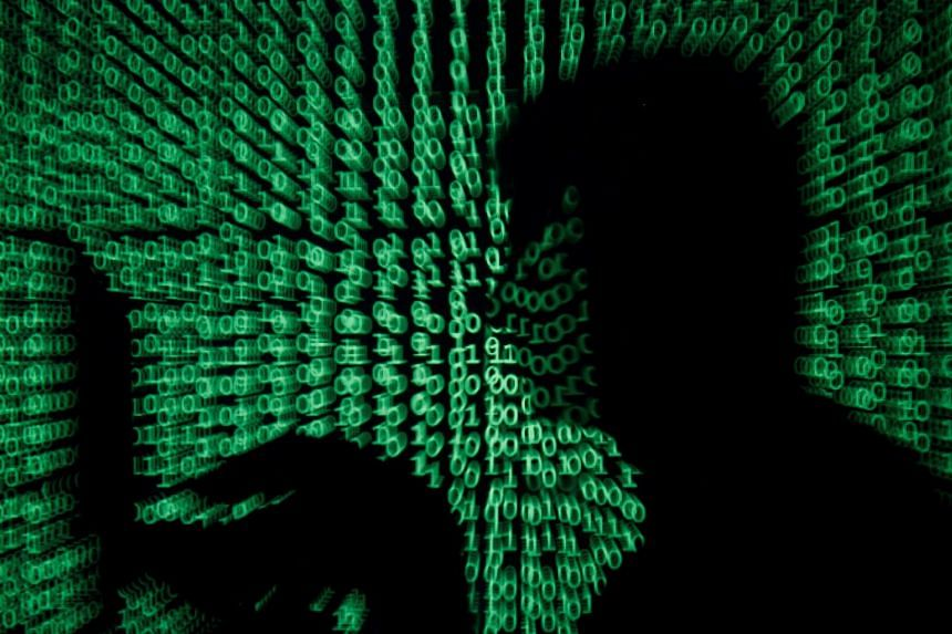 A man holds laptop computer as cyber code is projected on him in this illustration picture.