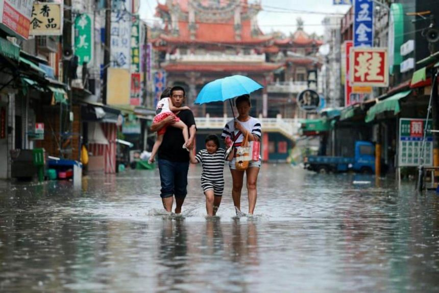 A family walks in floodwaters as Typhoon Nesat hits Pingtung county in southern Taiwan on July 29, 2017.