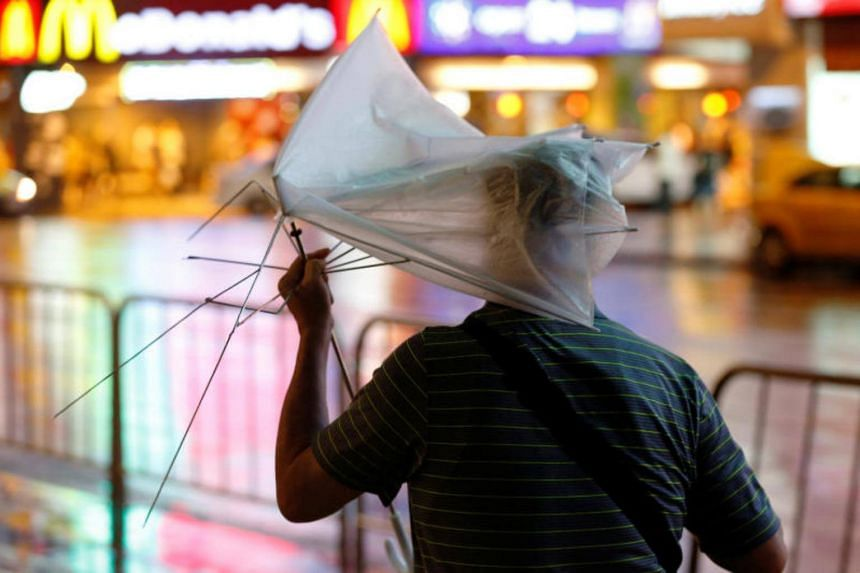 A man carrying a broken umbrella braves strong wind and rains as Typhoon Nesat hits Taipei, Taiwan on July 29, 2017.