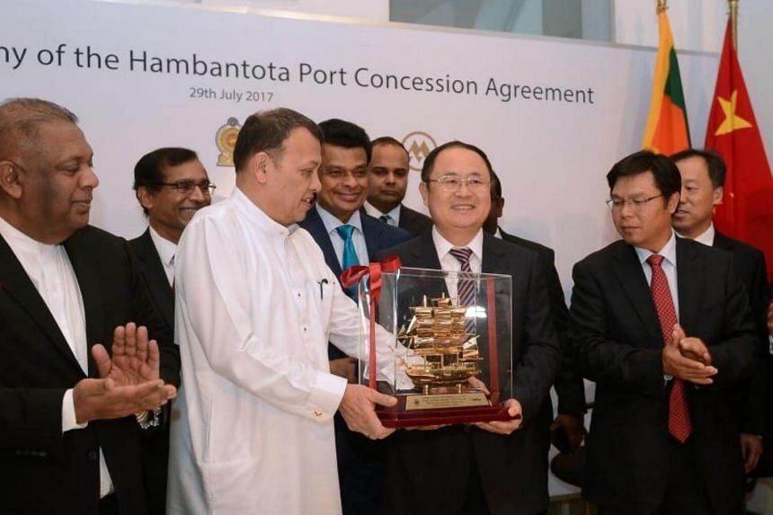 Sri Lanka's Minister of Ports & Shipping Mahinda Samarasinghe (centre) exchanges souvenirs with Executive Vice President of China Merchants Port Holdings Dr. Hu Jianhua (third from right) during the Hambantota International Port Concession Agreement