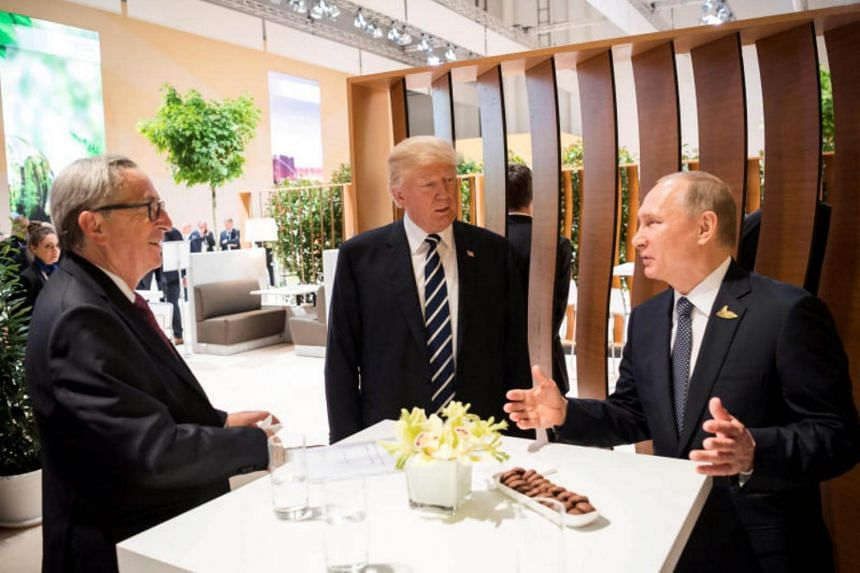 President Donald Trump with President Vladimir Putin of Russia, (right) and Jean-Claude Juncker, president of the European Commission, during the G-20 meeting in Hamburg, Germany on July 7, 2017.