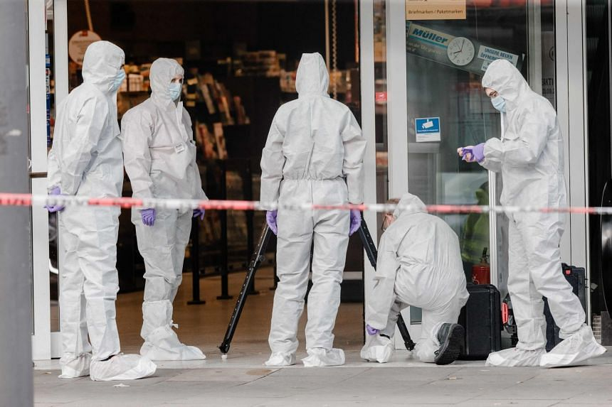 Police investigators work at the scene of the attack, where one person died.