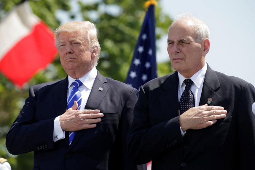 US President Donald Trump (left) and Mr John Kelly hold their hands over their hearts for the US National Anthem as they attend the Coast Guard Academy commencement ceremonies, on May 17, 2017.