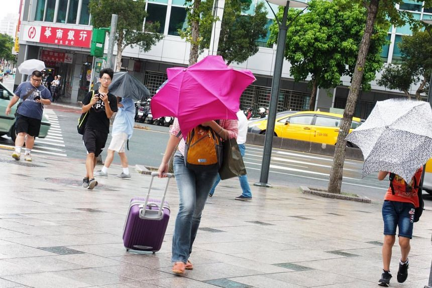 Pedestrians try to hold steady umbrellas as as Typhoon Nesat brought sporadic shower and strong wind to Taipei, Taiwan, on July 28, 2017.