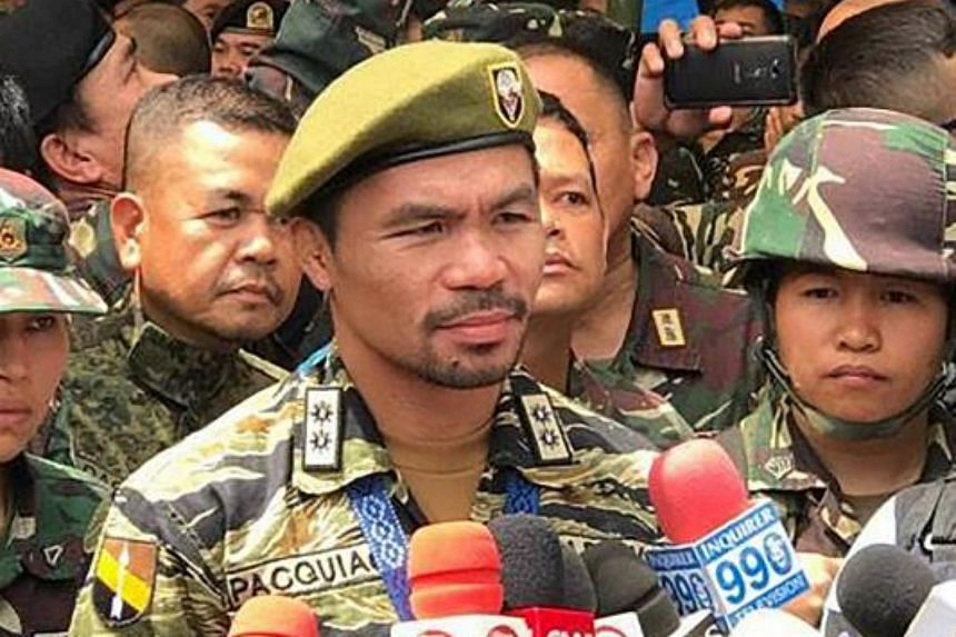 This handout from the Western Mindanao Command taken and released on July 29, 2017 shows Filipino boxer Manny Pacquiao (centre) talking to members of the media during a visit to a military camp in Marawi on the southern island of Mindanao.