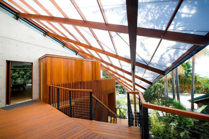 A sweeping, wing-like roof shelters a stairway in a four-bedroom, 4,600 sq ft eco-friendly home in Byron Bay, Australia. The house is warmed with hydronic heating built into the concrete slab, has many floor-to-ceiling gliding glass doors and require