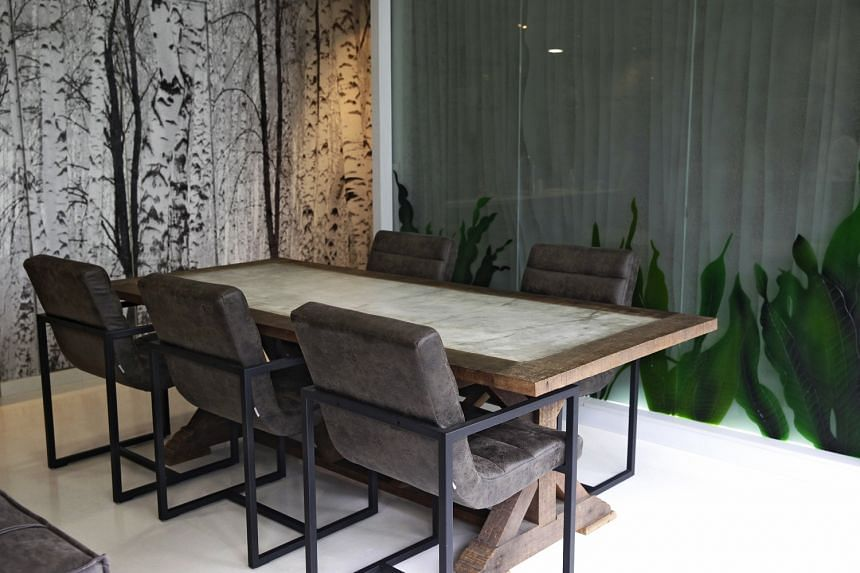The dining area (above) of Mr Xavier Chang's Pasir Ris apartment has a two-layered feature wall embellished with greenery. The study room has a tree wall decal that adds to the home's nature theme.
