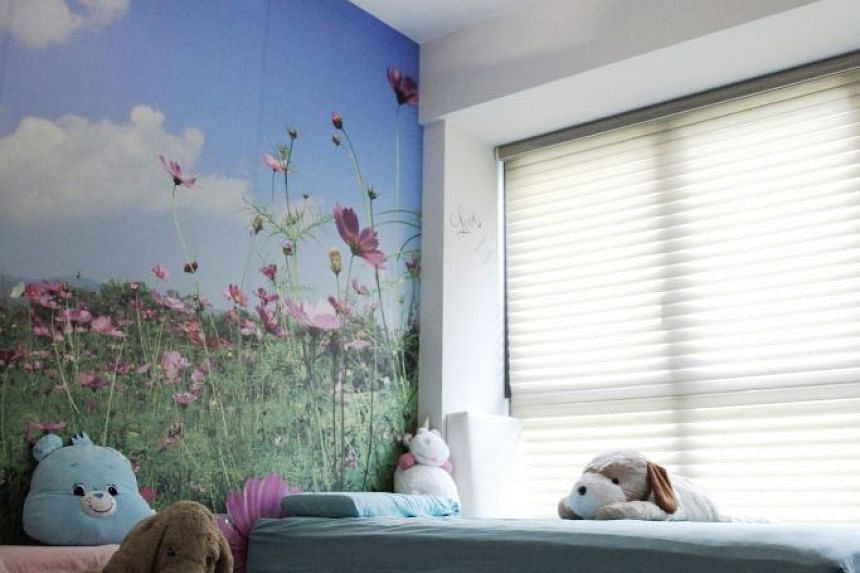 Wallpaper with meadows adorns the children's room.