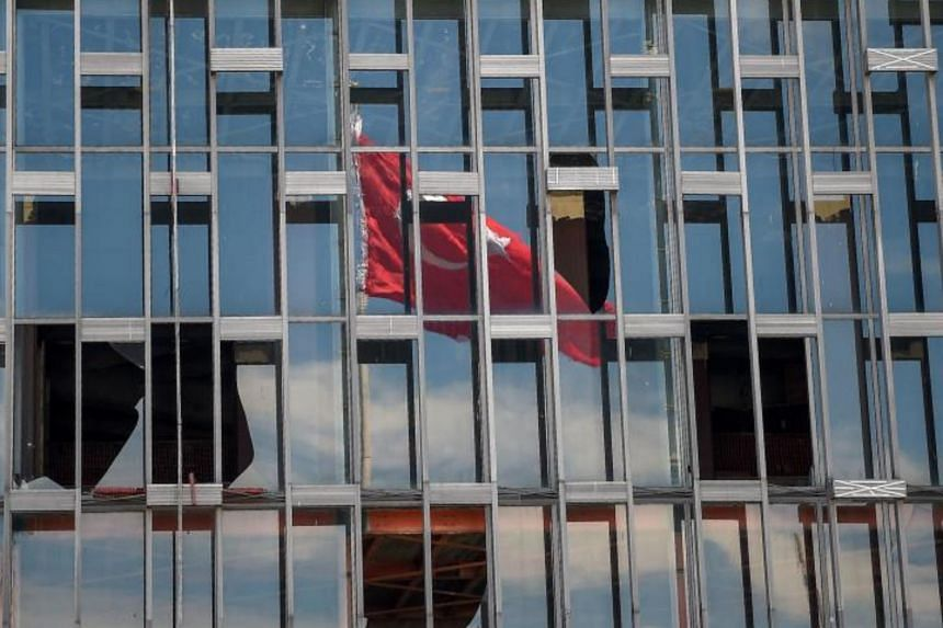 A reflection of the Turkish flag is seen reflected off of the Ataturk Cultural Center on June 13, 2017 in Istanbul.