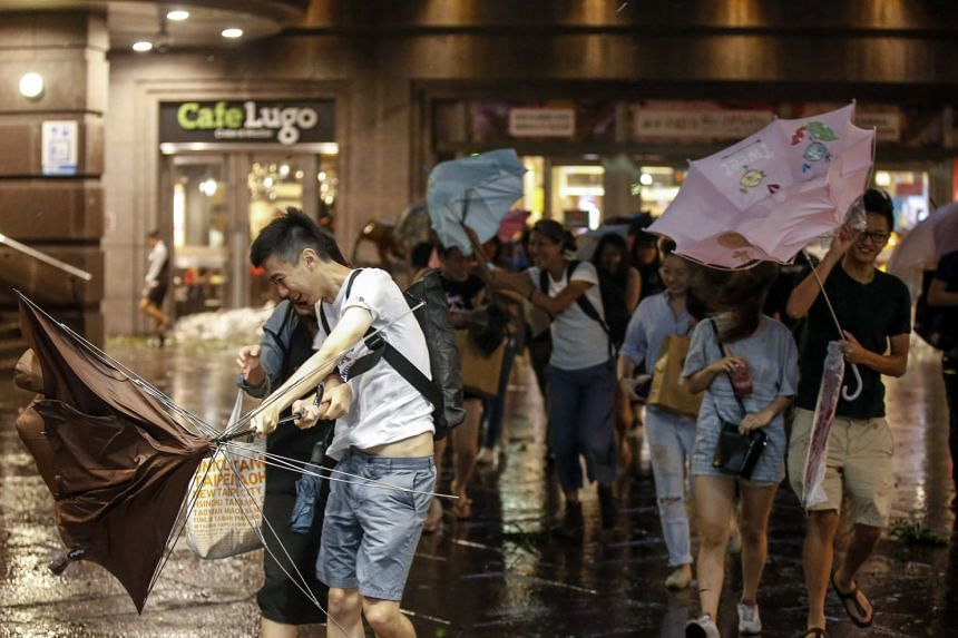 People shield themselves from strong winds and rain brought by Typhoon Nesat in Taipei.