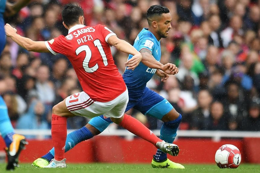Walcott skips away from Benfica's Pizzi during the Emirates Cup friendly.