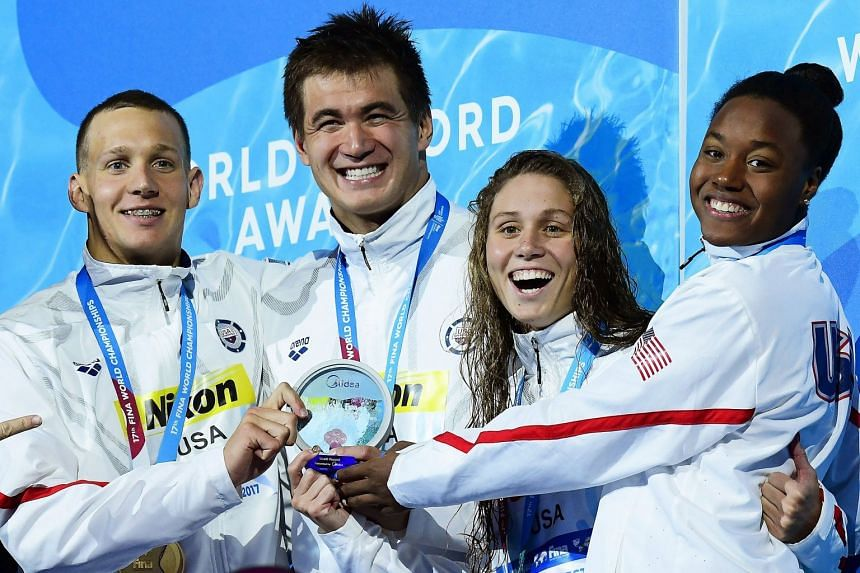US swimmers (from left) Caeleb Remel Dressel, Nathan Adrian, Mallory Comerford, and Simone Manuel celebrate on the podium.