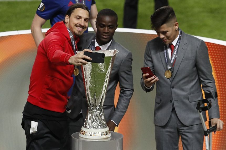 Manchester United's Zlatan Ibrahimovic takes a selfie with Eric Bailly and the Europa League trophy in May 2017.