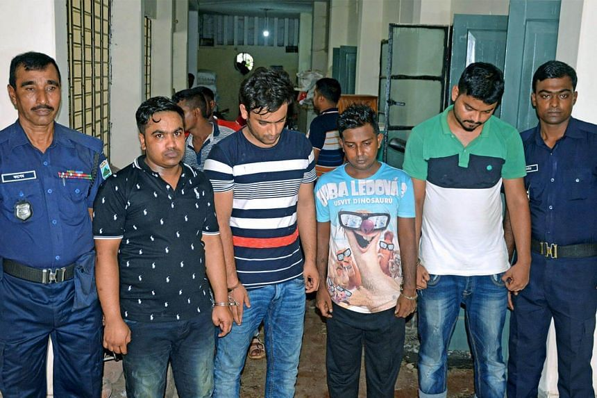 Tufan Sarker (second from left) a labour leader linked with the ruling Awami League party, along with three of his associates, is escorted by police following their arrest in Bogra, on July 29, 2017.