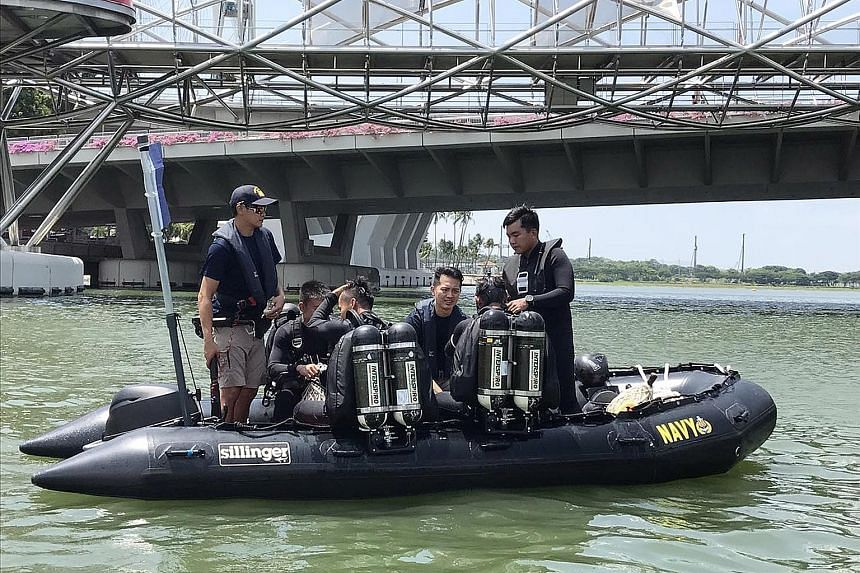 Some of the divers from the team of 10 from the elite Naval Diving Unit who scoped out the waters surrounding the platform ahead of the preview to ensure there were no suspicious objects in the water. Speaker of Parliament Halimah Yacob observing the