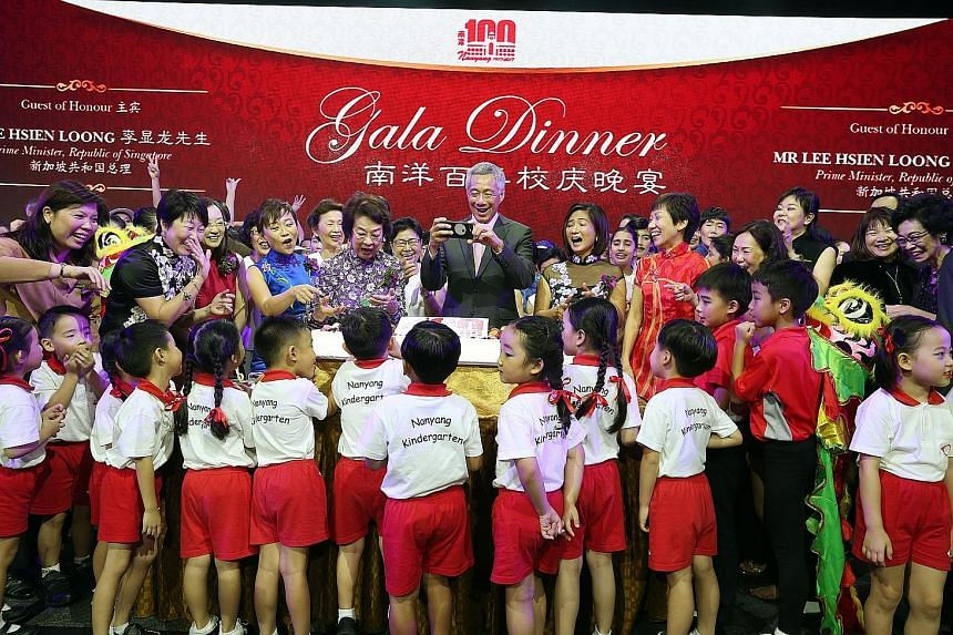 Prime Minister Lee Hsien Loong taking a shot of pupils with the anniversary cake. With him are (from fourth from left) Ms Chua Eng Eng, president of Nanyang Schools Alumni Association; Madam Wee Bee Hoon, honorary patron of Nanyang Family of Schools'