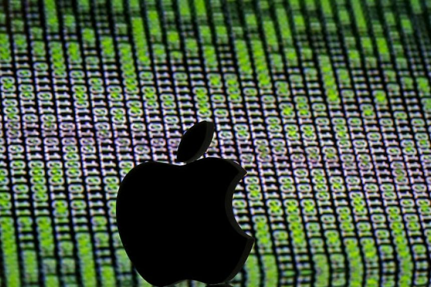 A 3D printed Apple logo is seen in front of a displayed cyber code in this illustration.