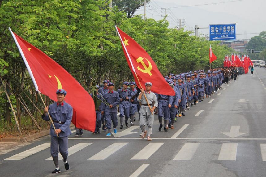 People dressed as Red Army soldiers carry flags as they march to mark the 90th anniversary of founding of Chinese People's Liberation Army (PLA), in Ruijin, Jiangxi province on July 28, 2017.