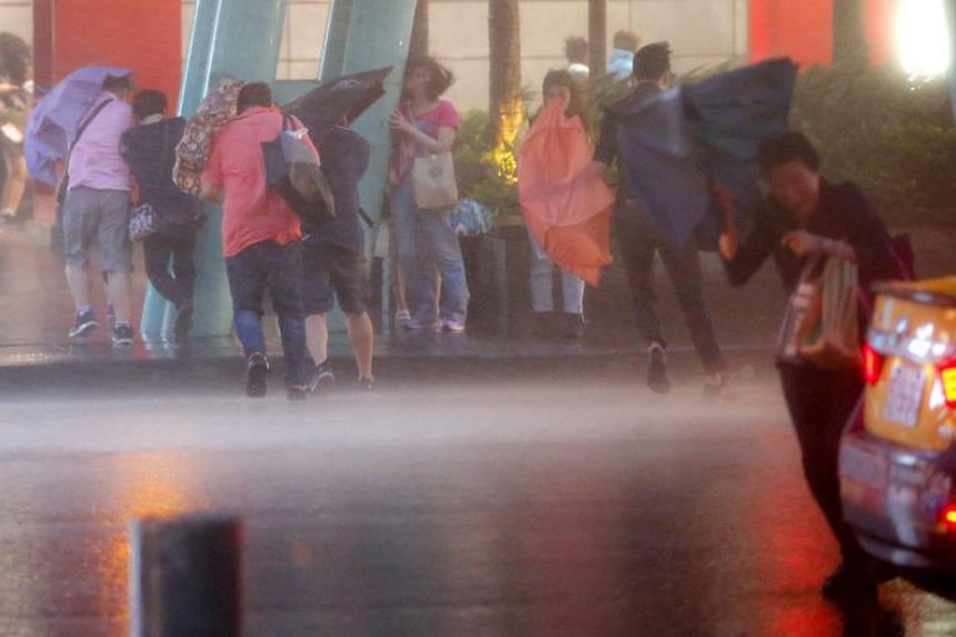 People shield themselves from strong wind and rain brought by Typhoon Nesat in Taipei, Taiwan.