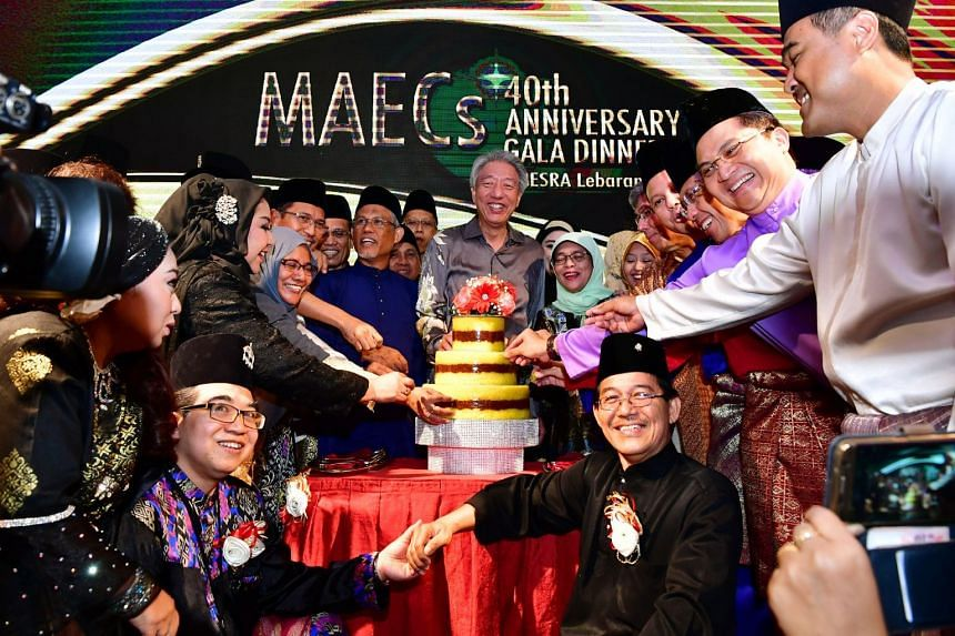 Symbolic scooping of Pulut Kuning cake on stage at the 40th anniversary gala dinner of the Malay Activity Executive Committees at Orchard Hotel on July 30, 2017.