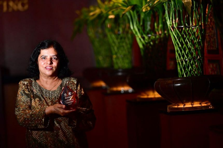 Madam Ayesha Abdullah, 61, Chairman of Pasir Ris East CC MAEC, with her award at the 40th anniversary gala dinner of the Malay Activity Executive Committees at Orchard Hotel on July 30, 2017.