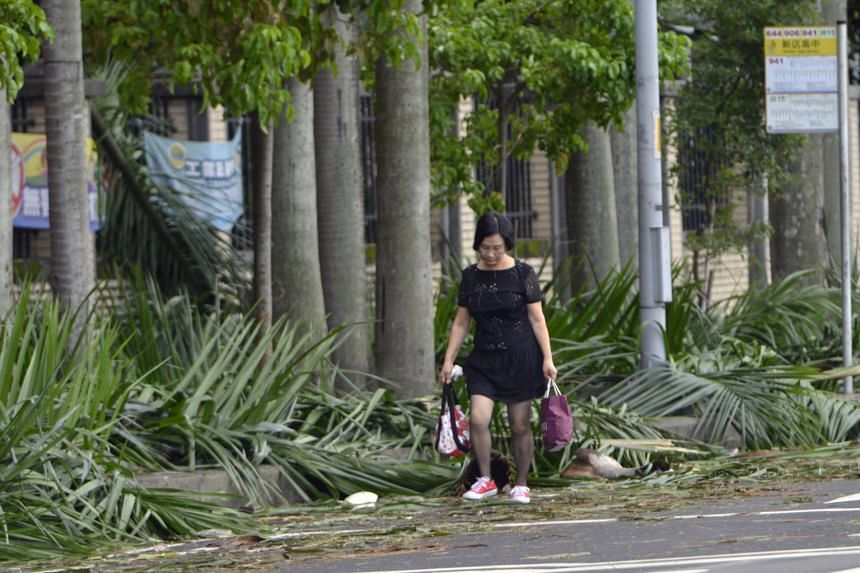 A woman walks past damaged trees on the street in New Taipei City on July 30, 2017.