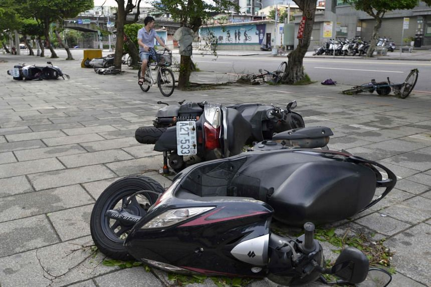 A man rides past motorcycles and bikes on a side walk in New Taipei City on July 30, 2017.