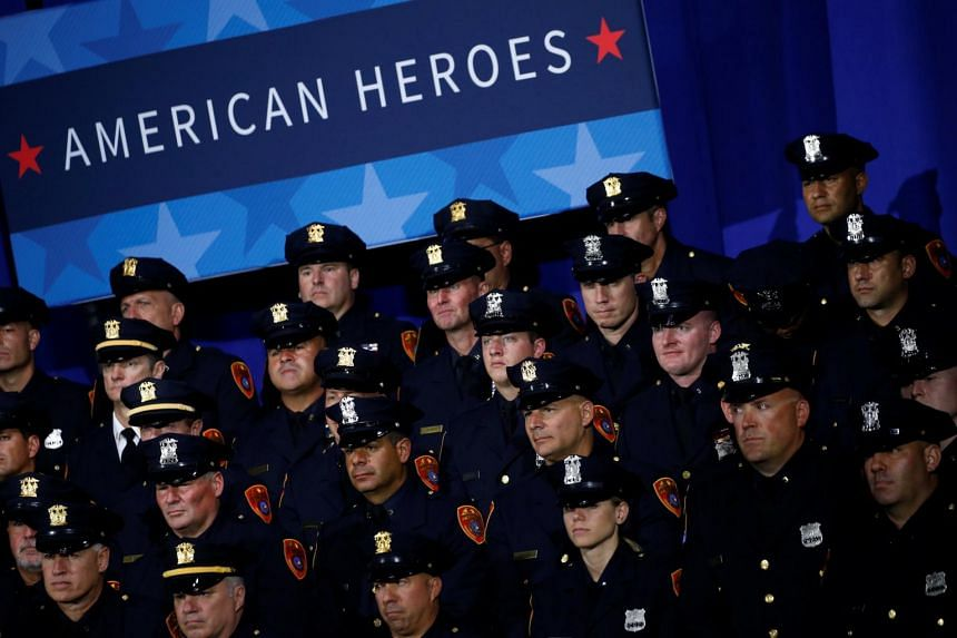 Police officers look on as US President Donald Trump delivers remarks about his proposed US government effort against the street gang Mara Salvatrucha.