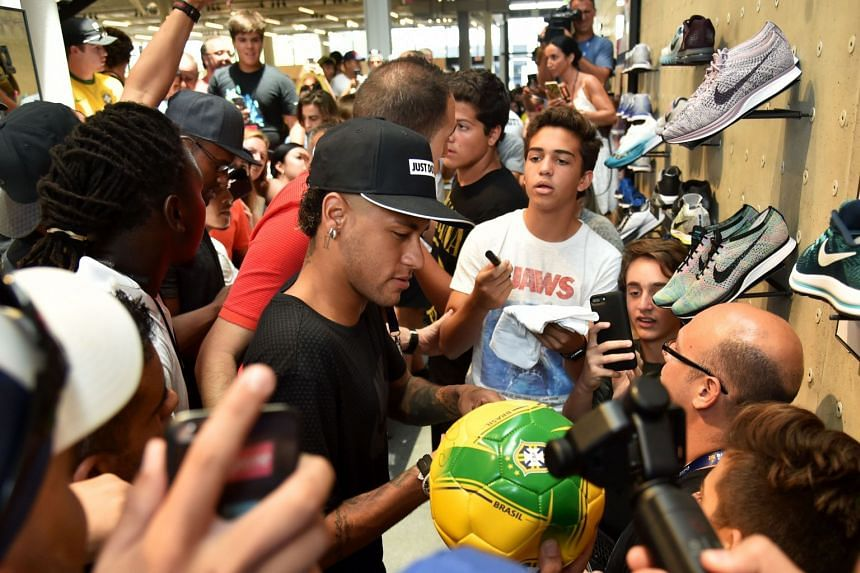Neymar signs autographs for fans at a sports shop event in Miami, July 28, 2017.