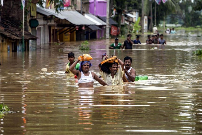 Indian flood victims walk amid water on their way to makeshift camp at flooded Amta village, 65km west of Calcutta, Eastern India, on July 30, 2017.