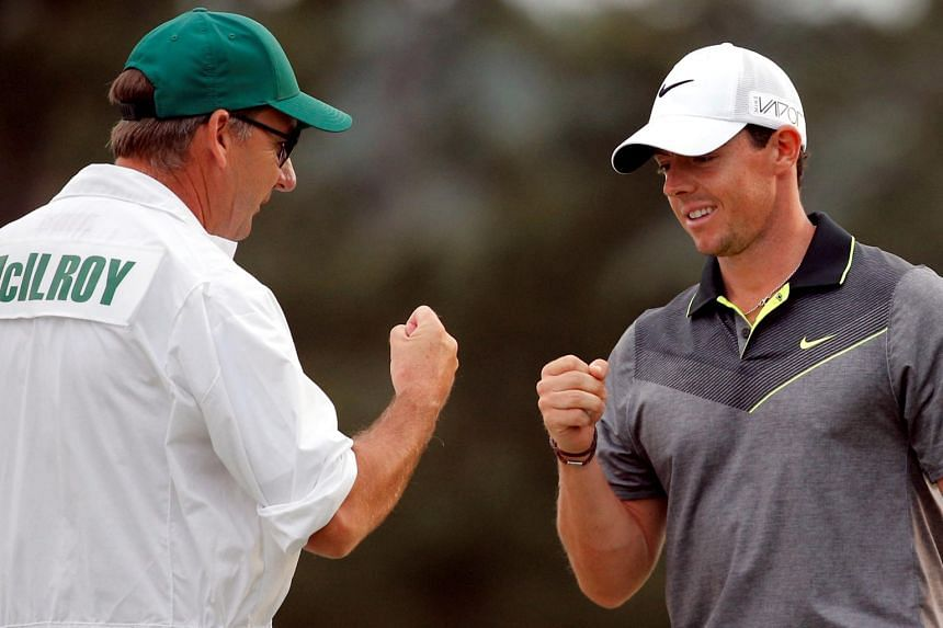 Rory McIlroy fists with his caddie J.P. Fitzgerald at the Augusta National Golf Course on April 10, 2015.
