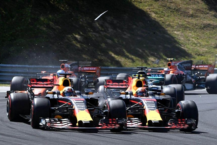 Red Bull's Australian driver Daniel Ricciardo (left) and Red Bull's Dutch driver Max Verstappen (right) collide as they race at the Hungaroring circuit in Budapest on July 30, 2017.