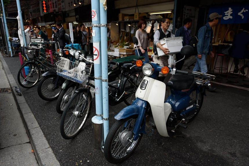 Honda Super Cub motorcycles and bicycles sit parked in front of stores at Tsukiji Market in Tokyo, on June 13, 2017.