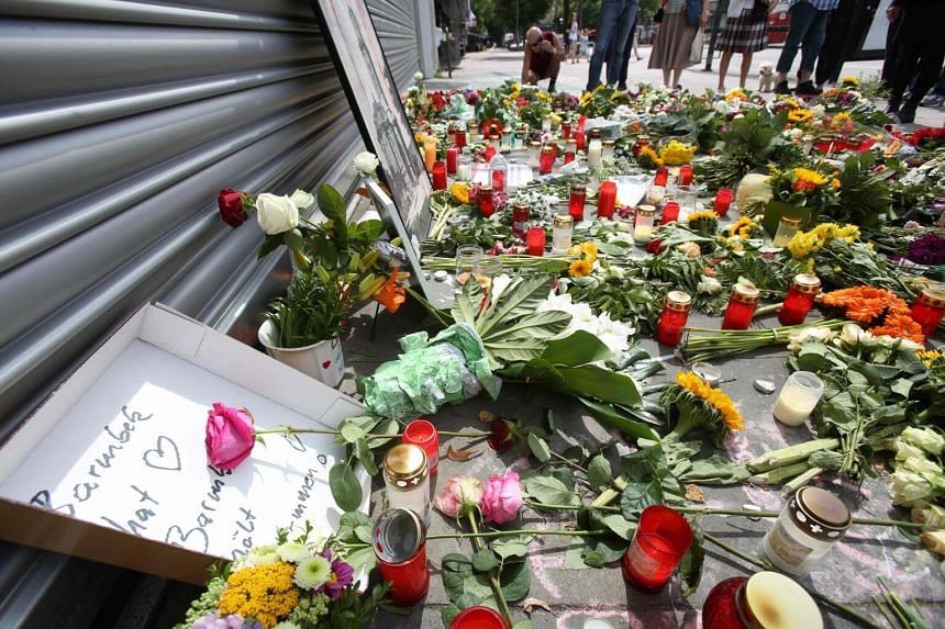 A makeshift memorial of flowers and candles for the victims of a knife attack in front of a supermarket in Hamburg's Barmbek district, northern Germany on July 30, 2017.