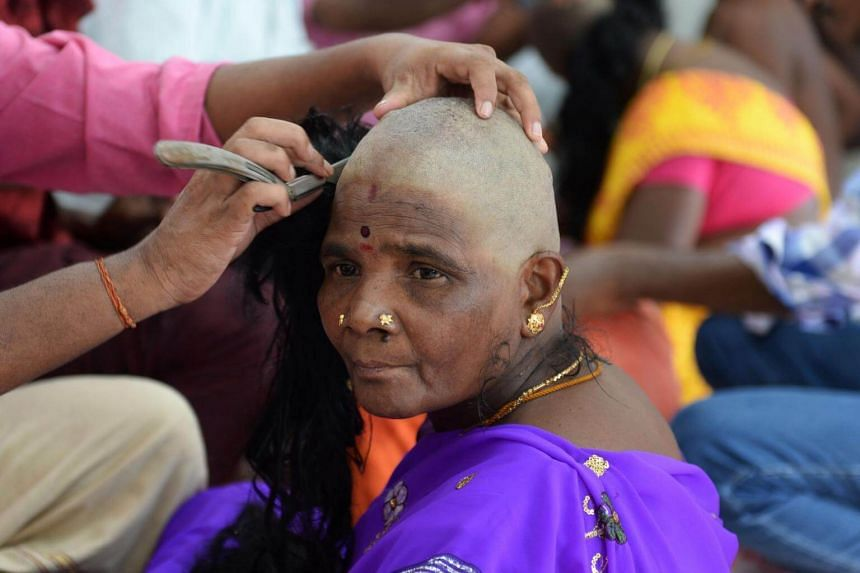 An Indian Hindu devotee gets her head shaved at the Thiruthani Murugan Temple in Thiruthani in India's southern state of Tamil Nadu, on July 19, 2017.