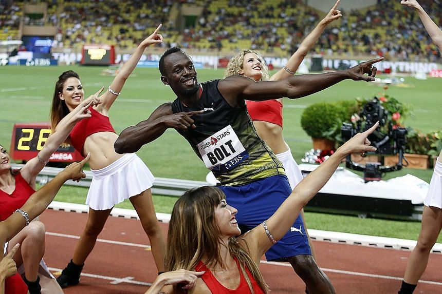 Usain Bolt strikes his signature pose with cheerleaders at the IAAF Diamond League meet in Monaco on July 21.