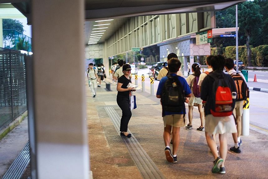"""A woman giving out fliers promoting a centre last Wednesday outside Hwa Chong Institution's gate near Tan Kah Kee MRT station. The school said it is monitoring the situation """"to ensure that there is no security and safety threat posed to the school c"""