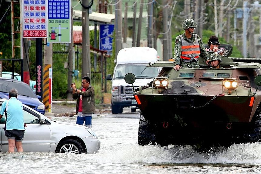 Soldiers on their way to deliver food and water to people stranded in flood-hit areas in Pingtung, southern Taiwan, yesterday.