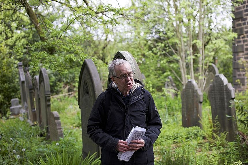 A volunteer leading a tour of a graveyard in the town of Todmorden in West Yorkshire, Britain. The tours are part of a community-generated festival, called Pushing Up Daisies, that aims to start conversations about death, dying and bereavement. The f