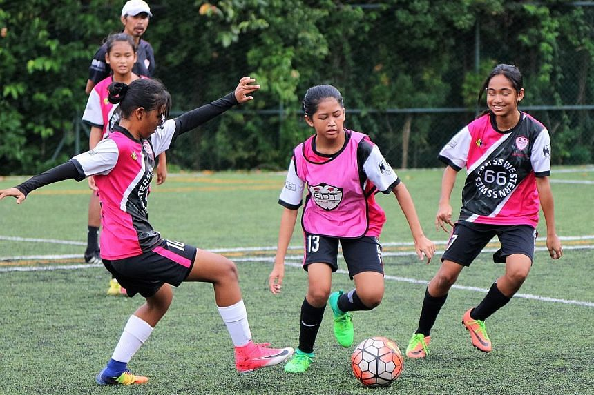 Above: (From left) Dhaniyah Qasimah Zamri Abdullah, 13, Eba Safieya Ebramshah, 13, and Nur Atikah Ardini Salleh, 14, with Nurhidayu Naszri, 13, in the background, during training on June 11 for the Wawu Cup China International Friendship City Youth Footba