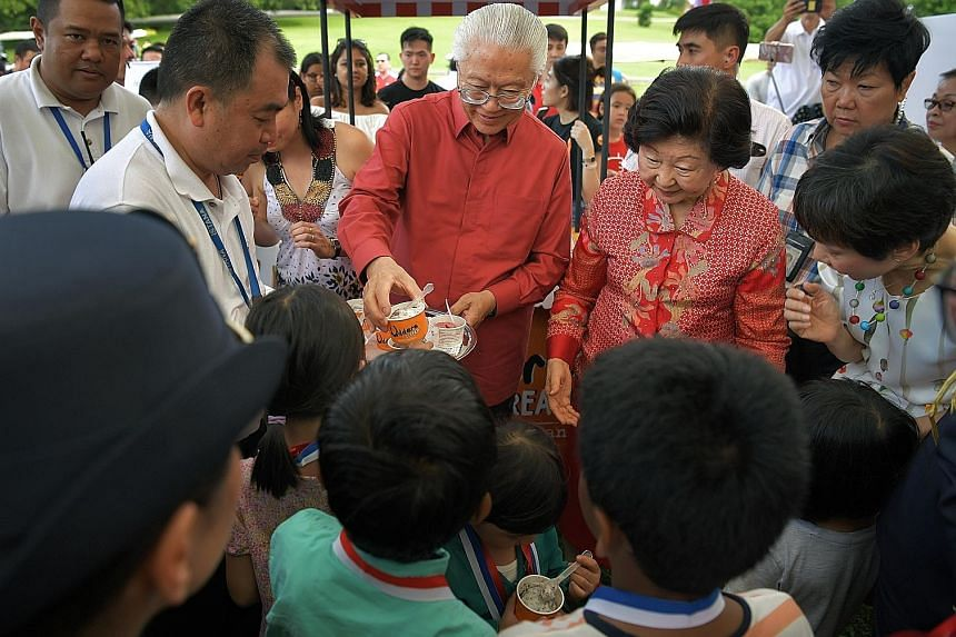 Visitors enjoying the greenery at the Istana during the open house yesterday. Left: President Tony Tan Keng Yam and his wife, Mrs Mary Tan, distributing Istana Harvest, a sorbet in celebration of Singapore's 52nd birthday, to children. Above: People