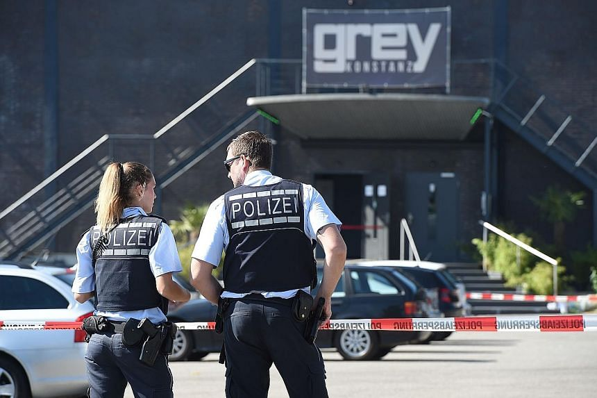 Policemen in front of the Grey disco in the southern German town of Konstanz, where a gunman opened fire, killing one person and wounding three seriously.