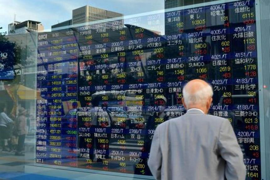 A man looks at a stock prices board showing the numbers on the Nikkei 225 at the Tokyo Stock Exchange.