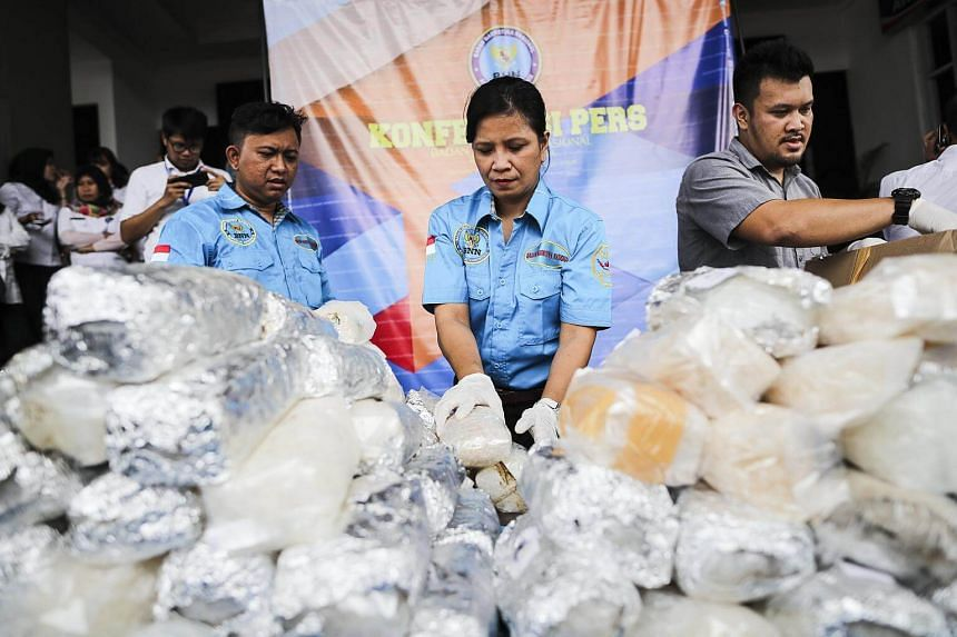Indonesian National Narcotic Agency (BNN) officers inspect methamphetamine packages during a press conference following a raid in Jakarta, Indonesia, on July 27, 2017.