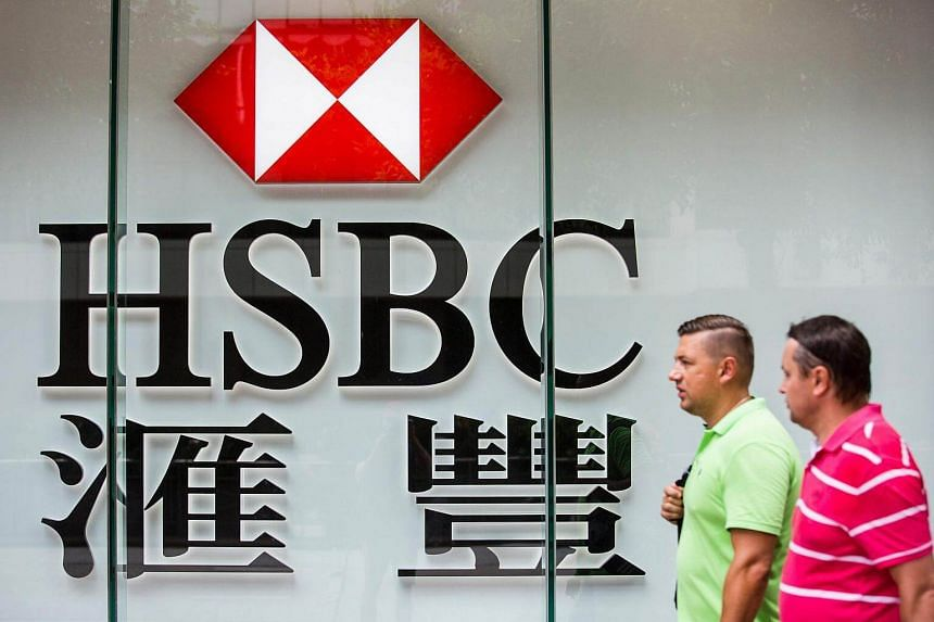 Pedestrians walking past a HSBC signage in the Admiralty district of Hong Kong, on July 31, 2017.