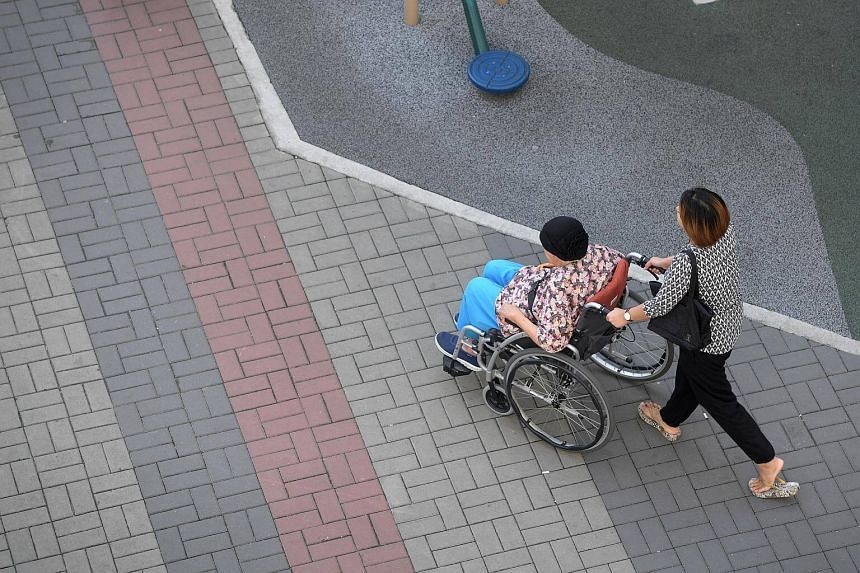A caregiver pushing an elderly on a wheelchair.