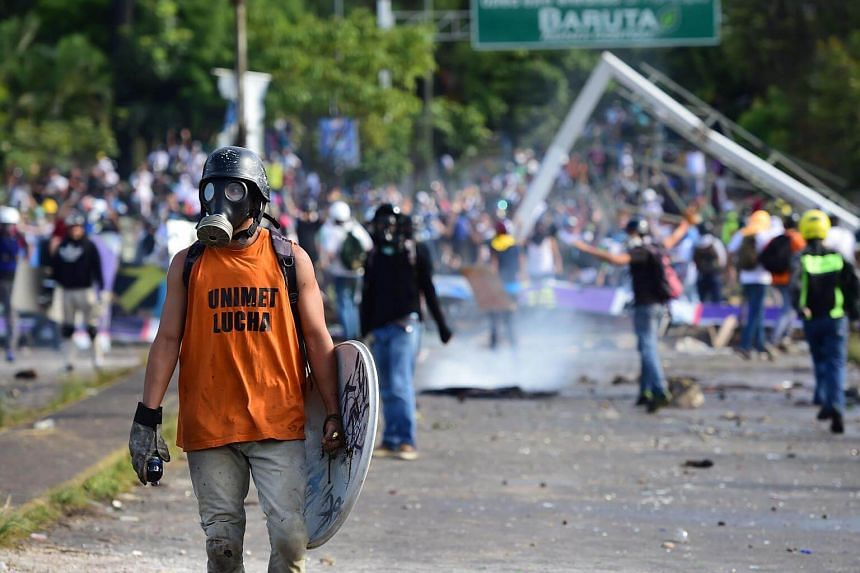 Anti-government activists clash with security forces during a protest in Caracas, on July 30, 2017.