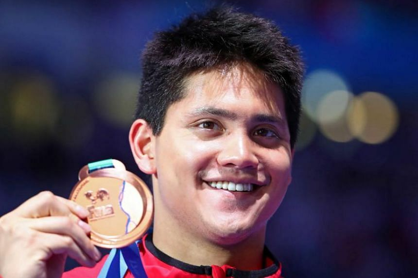 Joseph Schooling posing with his bronze medal in the men's 100m butterfly event at the Fina World Championships.
