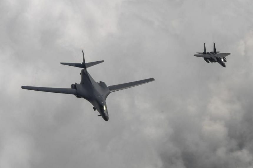 An American B1-B bomber (left) escorted by a South Korean F-15K fighter (right) fly over South Korea into Japanese airspace and over the Korean Peninsula on July 30, 2017